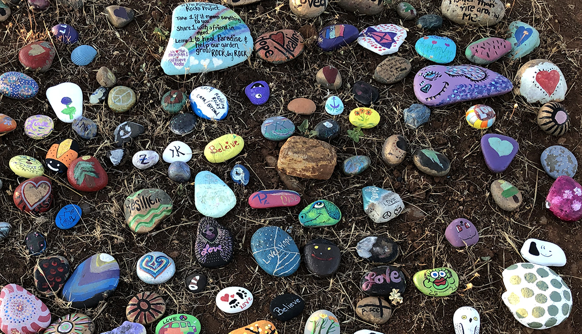 item 8 of Gallery image - a few dozen rocks of different sizes, brightly painted with colorful designs and messages or words of hope and love are placed on the ground next to the memorial crosses in paradise california