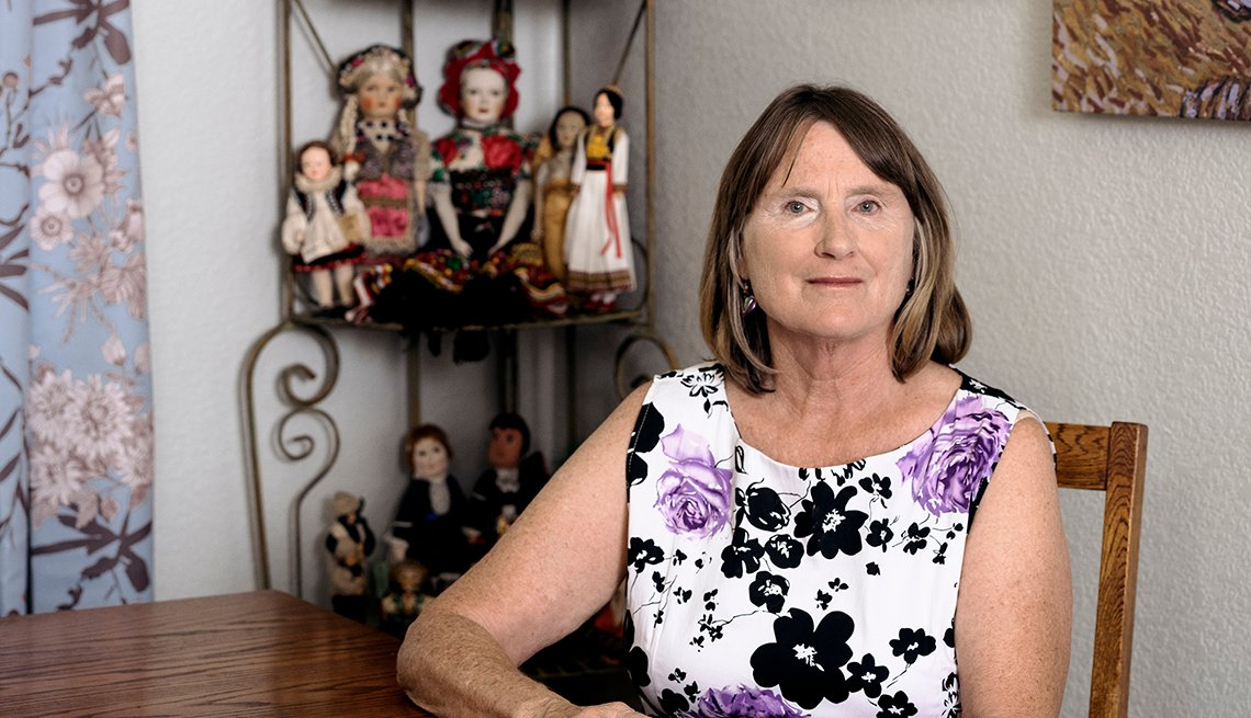 claudia oreilly sits at the table with a collection of dolls behind her on a shelf