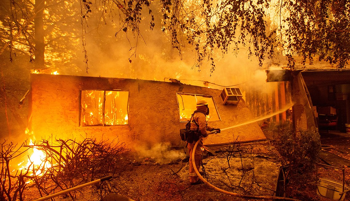 Firefighter fights a wildfire next to what's left of a house