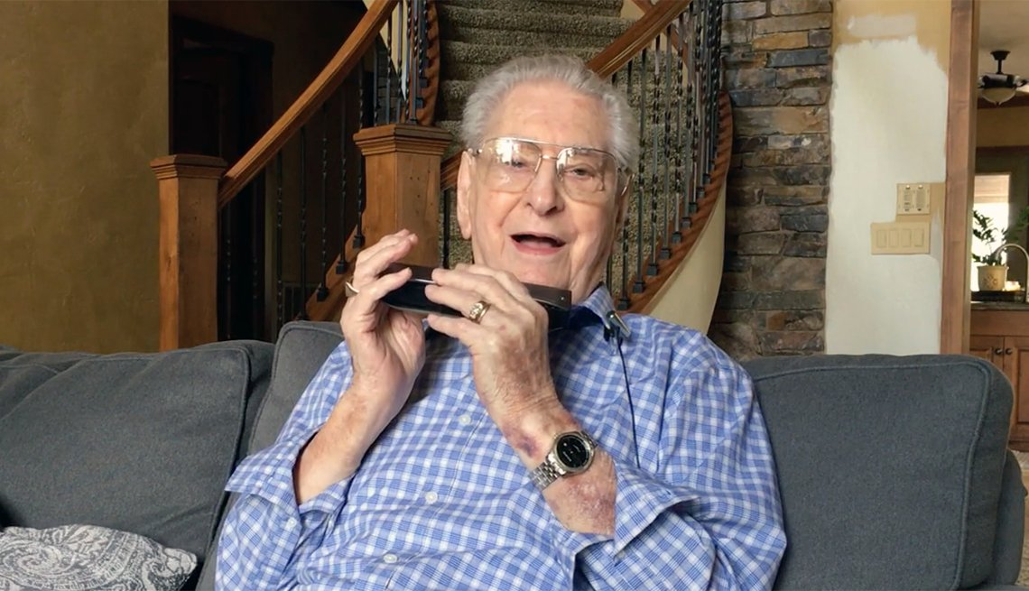 portrait of harold maurer seated on a couch holding his harmonica