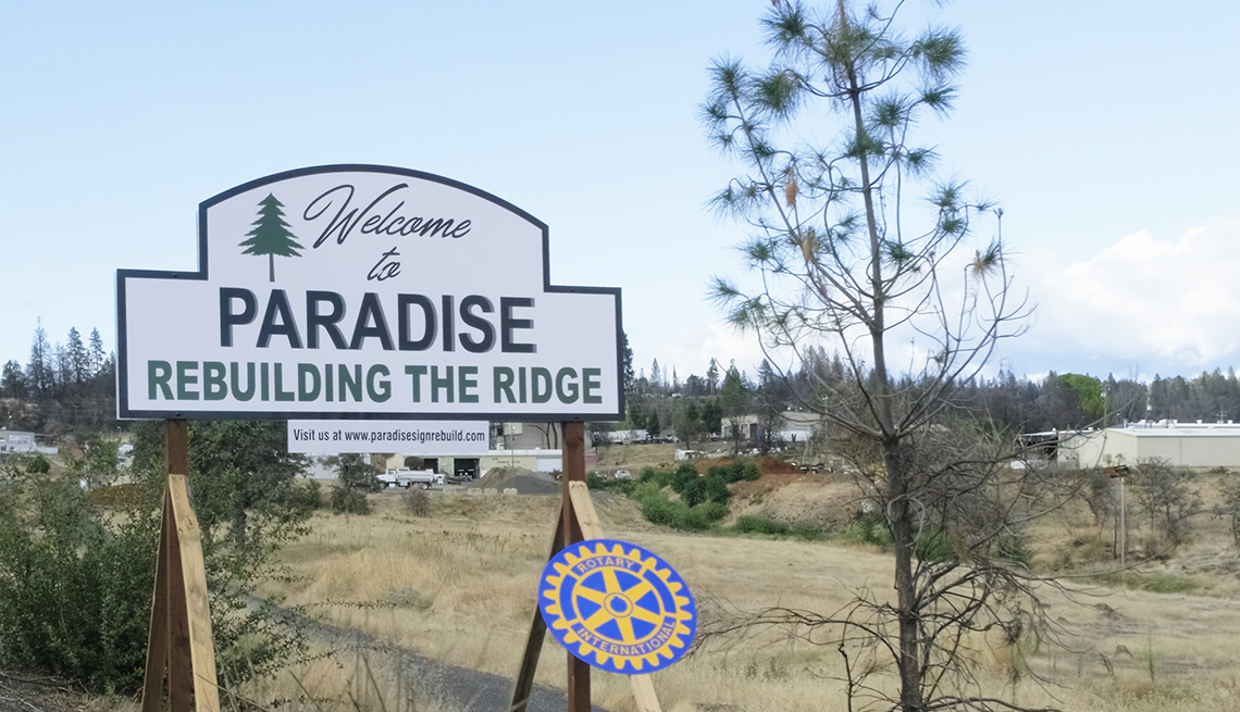 A white sign that says welcome to paradise rebuilding the ridge