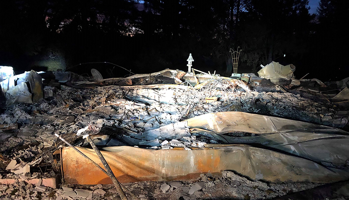 item 4 of Gallery image - night scene of a completely burned out house in the aftermath of the paradise camp fire. it is a pile of rubble.