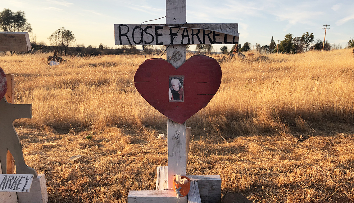 item 9 of Gallery image - a wooden memorial cross bearing the name of rose farrell aged 99 who was paradises oldest fatality during the camp fire