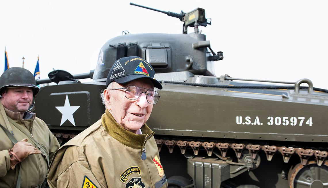 An older man stands next to a tank from World War Two