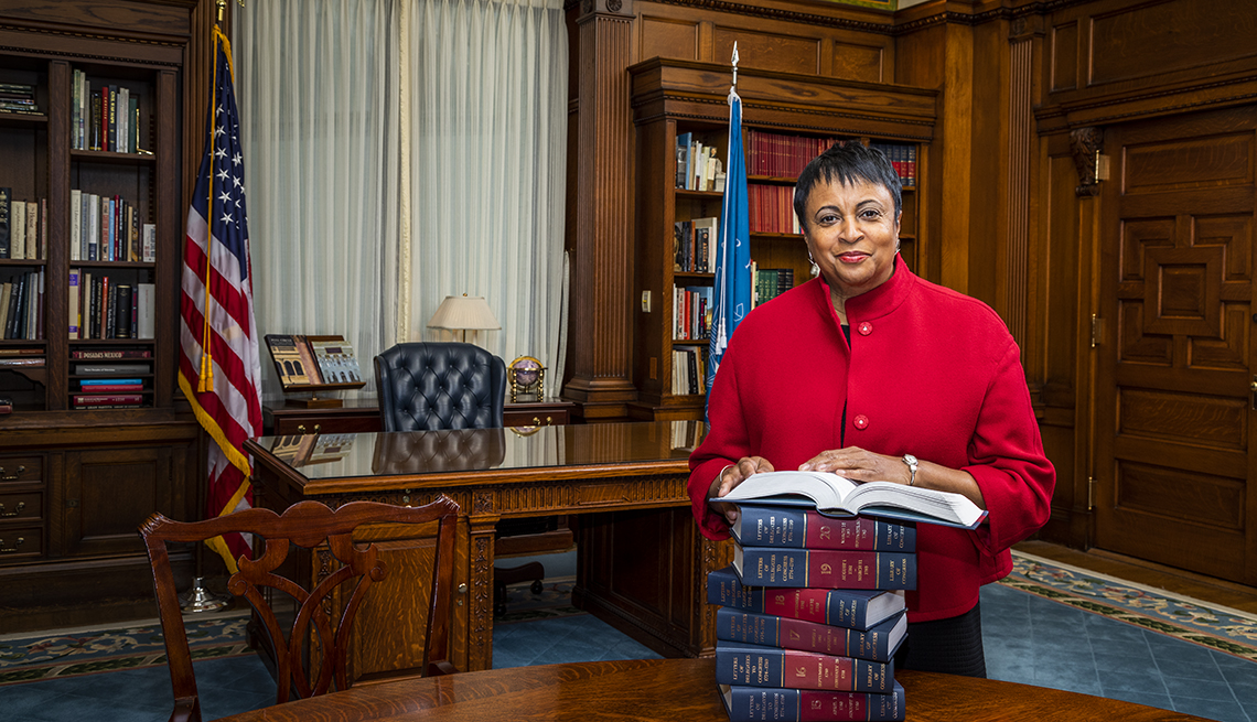 Librarian of Congress Carla Hayden stands in her office with a stack of books