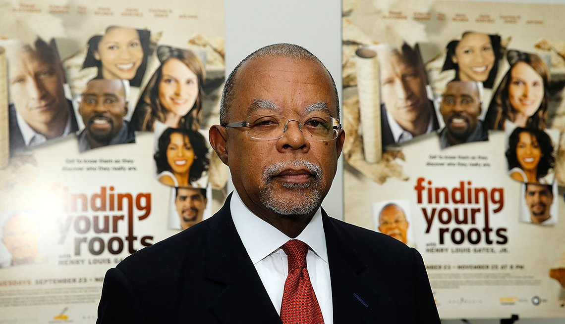Henry Louis Gates Junior stands by two posters of his show finding your roots