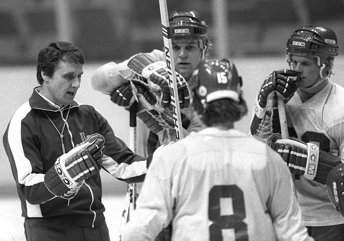 United States Olympic ice hockey coach, Herb Brooks, left, speaks to members of the team during a break in practice at the Ice Hall in Lake Placid