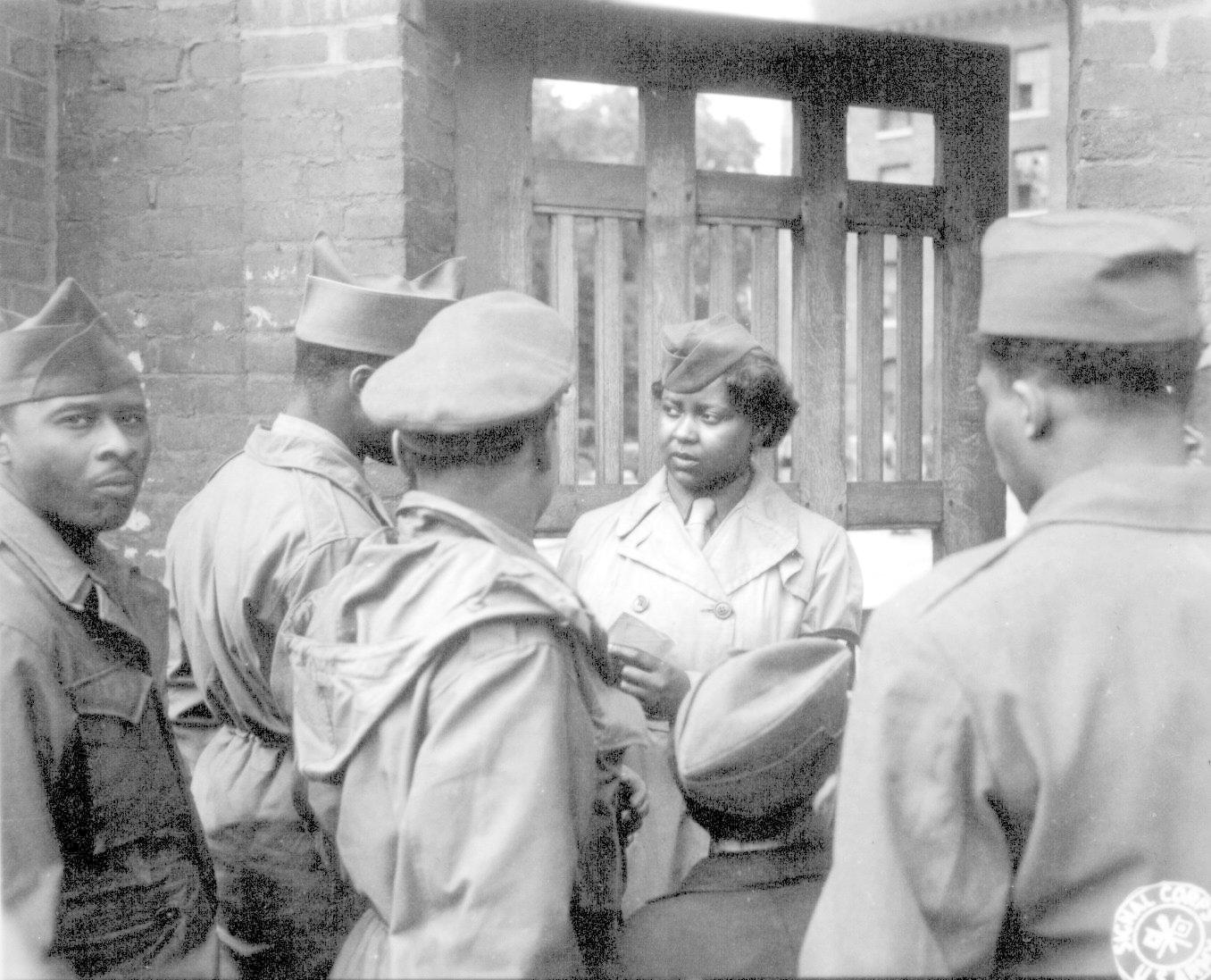 A group of African American soldiers are talking outside of a door during World War Two