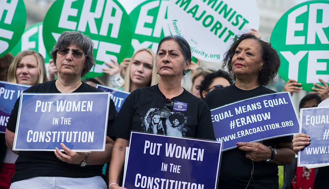 Women hold signs saying E R A Yes and Put Women in the Constitution