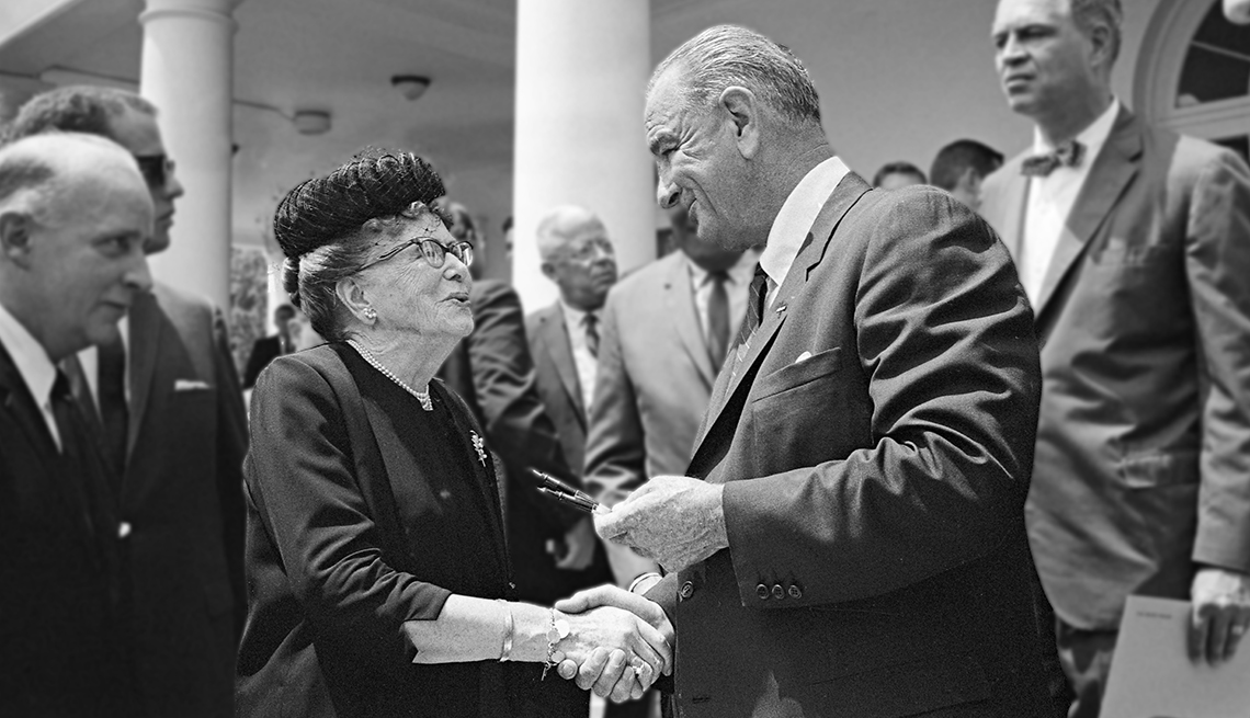 President Lyndon Johnson offers Dr. Ethel Percy Andrus a pen he used to sign the Older Americans Act.