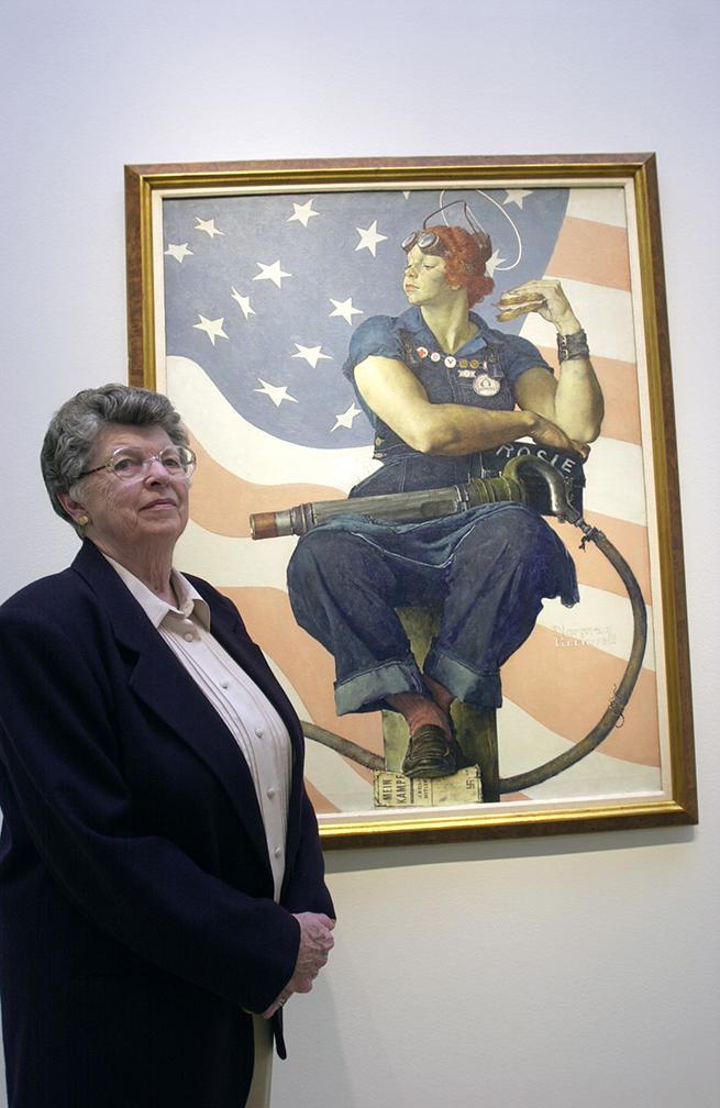 Mary Keefe, de 78 años, está parada junto a un póster de la película Rosie the Riveter de 1944