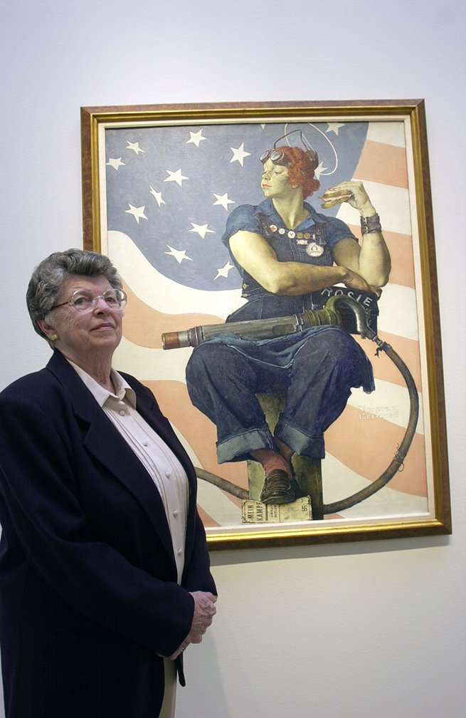 """Mary Keefe, 78, stands next to Norman Rockwell's painting """"Rosie the Riveter"""" at Sotheby's auction house."""