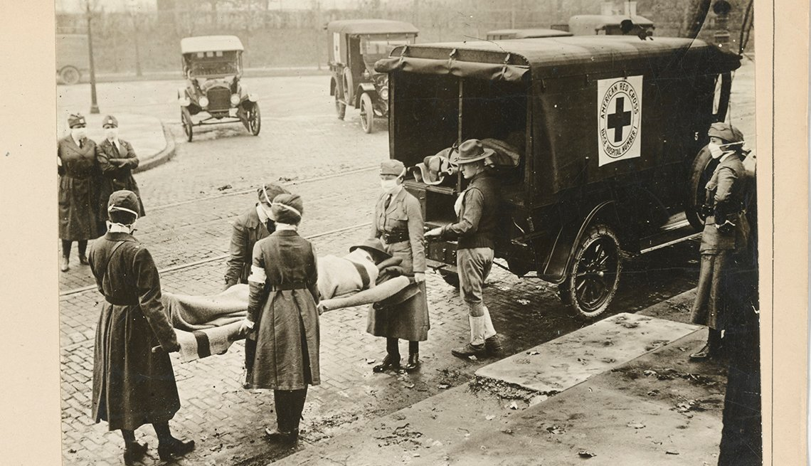 a patient on a gurney is loaded into a red cross motor corps ambulance