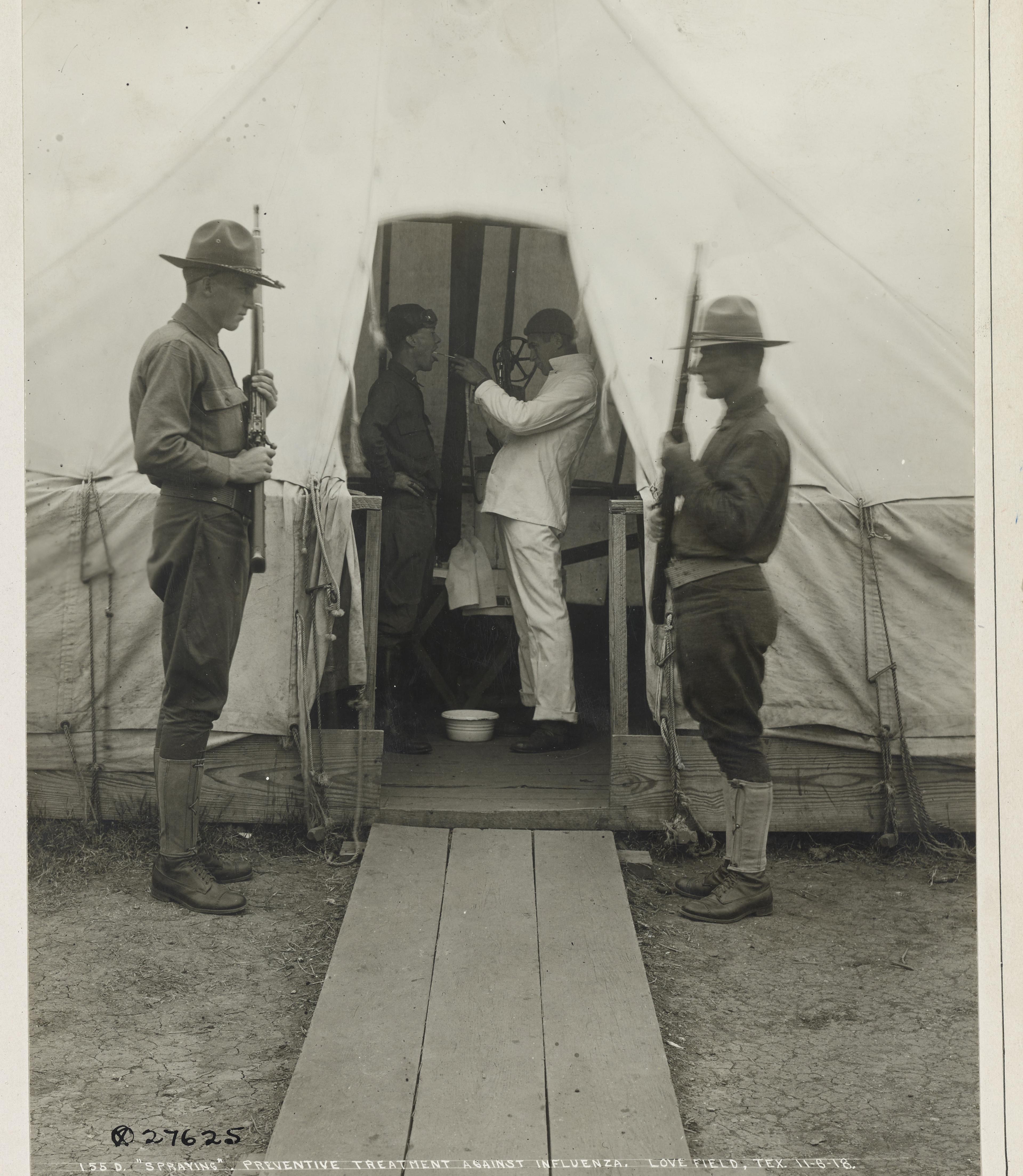 item 6 of Gallery image - Un oficial médico rocía desinfectante en la boca de un soldado en una carpa médica