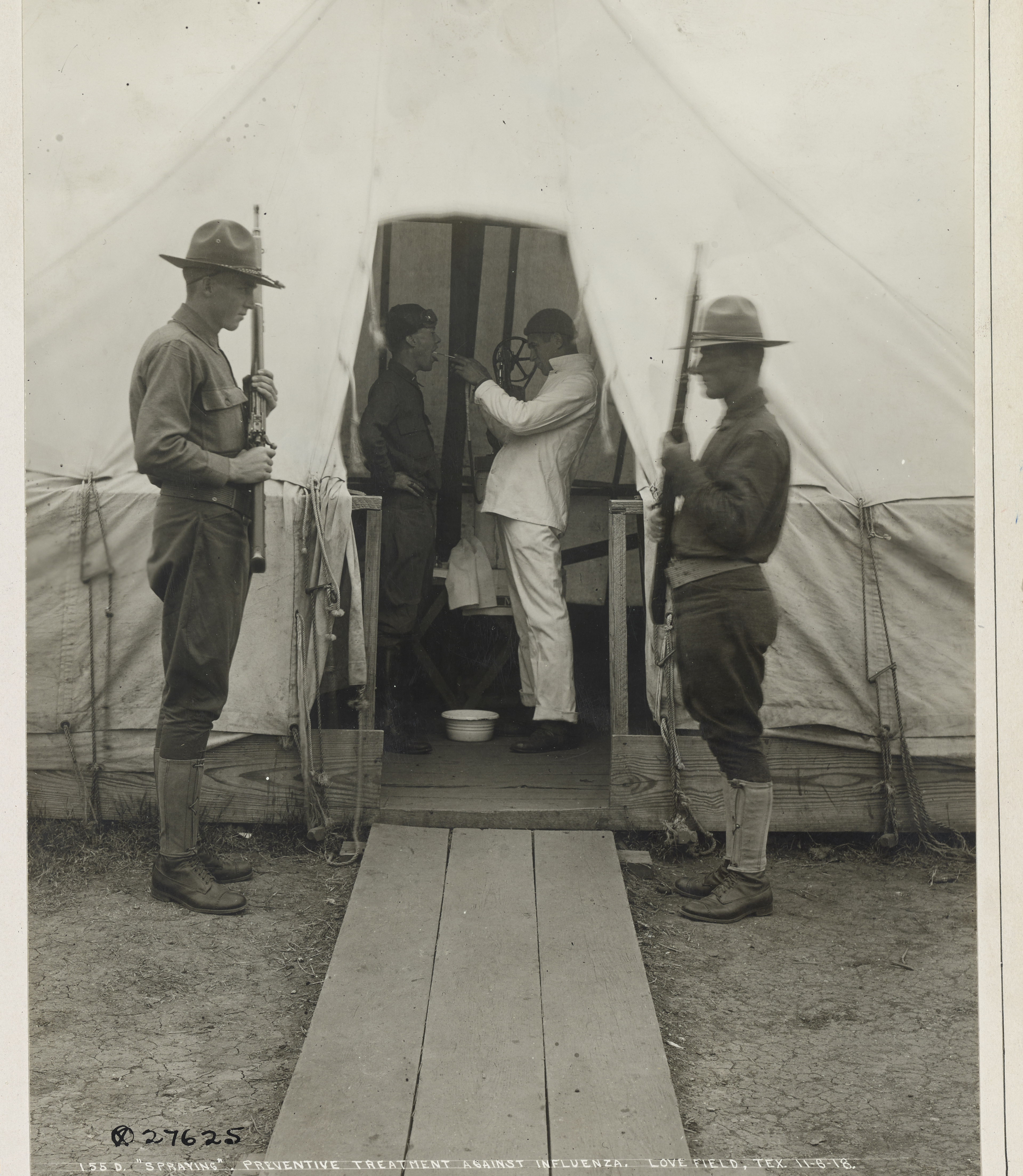 item 6 of Gallery image - a medical officer sprays disinfectant into the mouth of a soldier in a medical tent