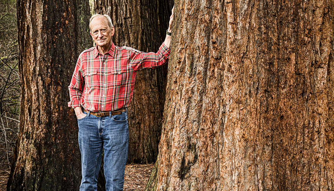 denis hayes poses in a forest with his hand on a large tree trunk
