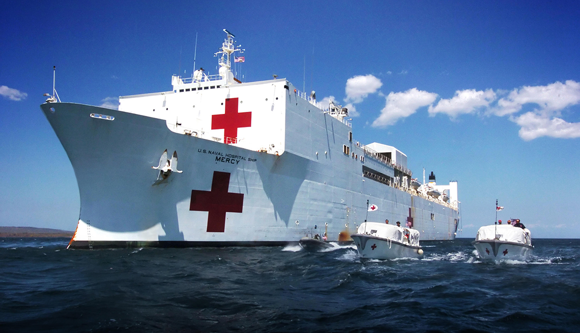 item 7 of Gallery image - at sea shot of the front of a u s navy hospital ship and two smaller transport boats