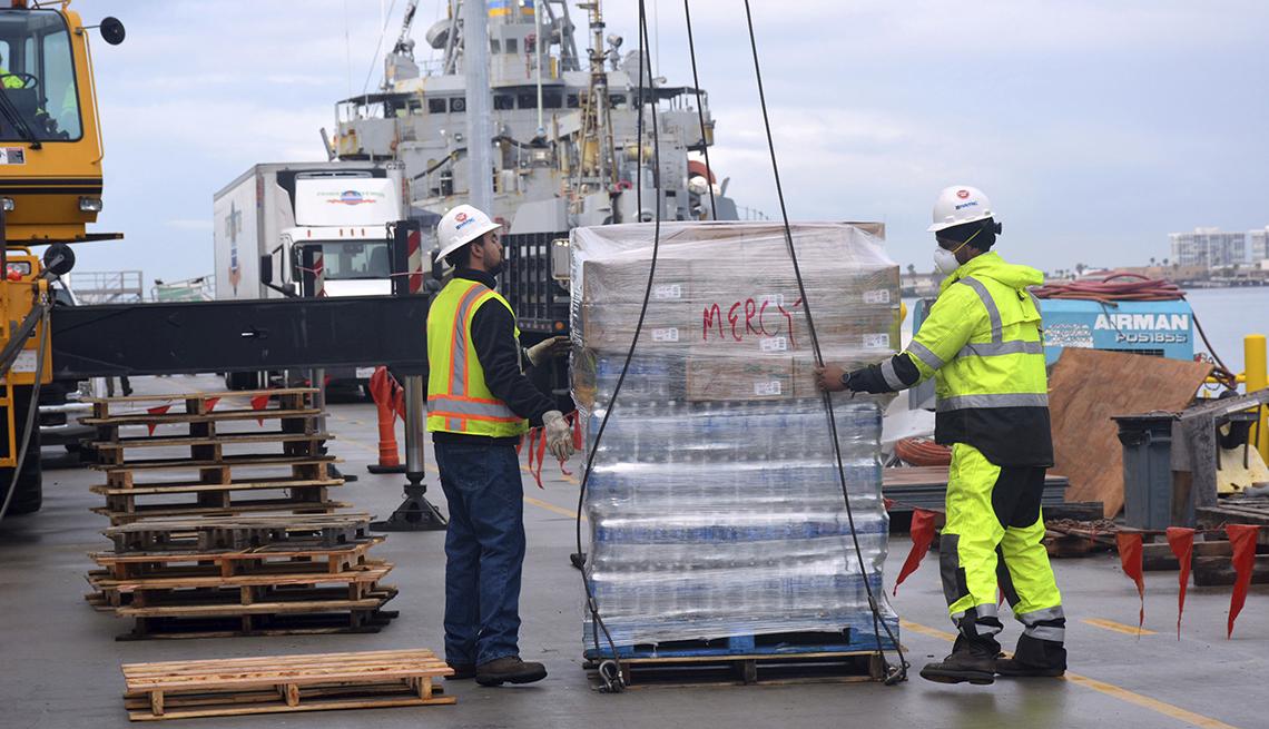 item 2 of Gallery image - Dos trabajadores montan carga al buque hospital USNS Mercy
