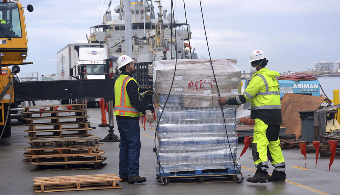 item 2 of Gallery image - two dock workers wearing hard hats and reflective safety clothing oversee supplies being loaded onto a ship by crane lift
