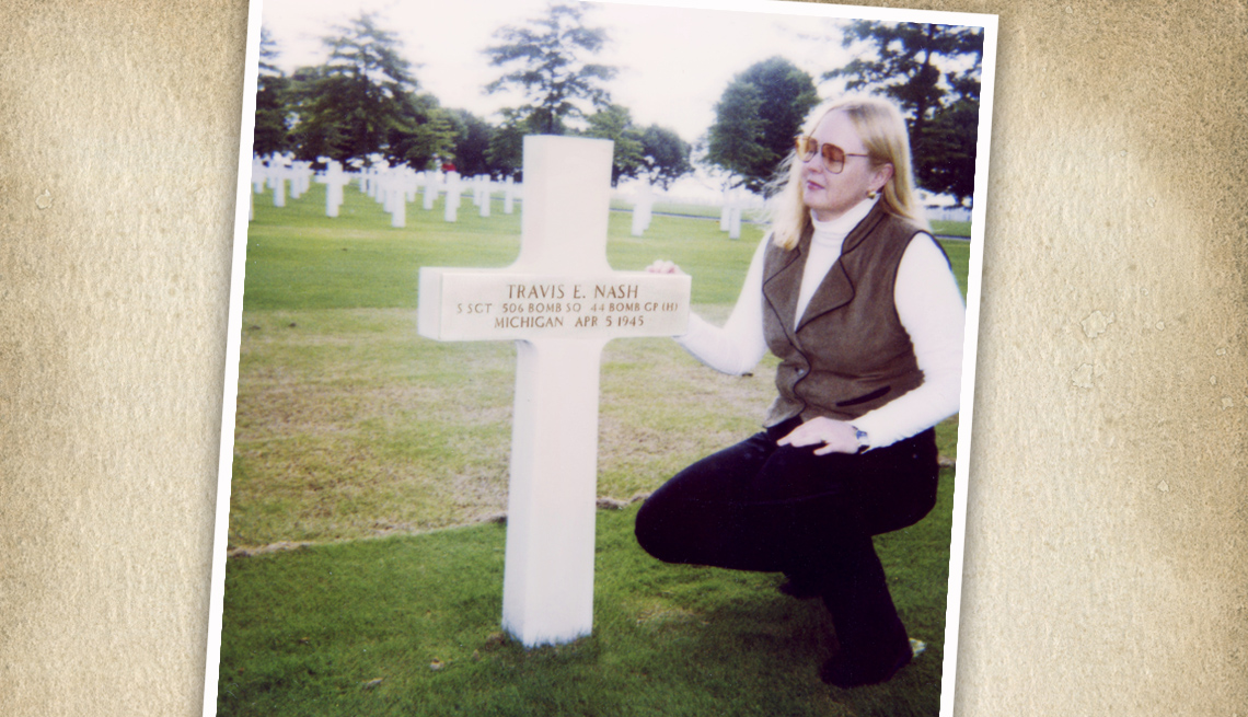 item 7 of Gallery image - a woman kneels at the white cross grave of a fallen world war two soldier