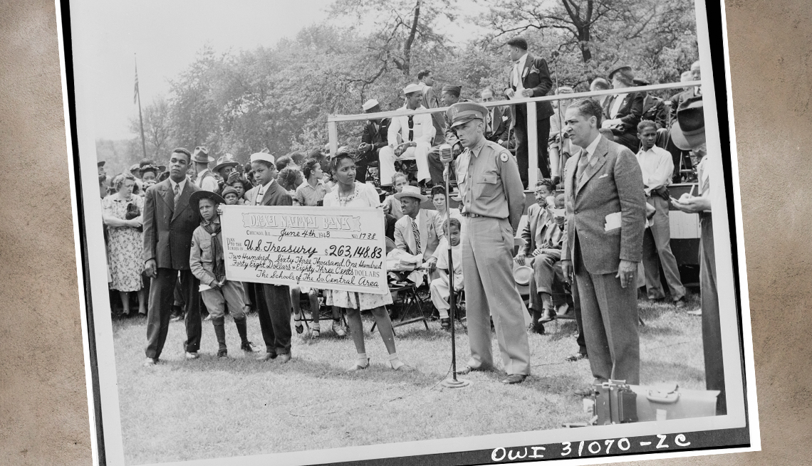 item 9 of Gallery image - crowd of people at a world war two rally with several children in the front holding an oversized ceremonial check for army supplies from money raised by their school