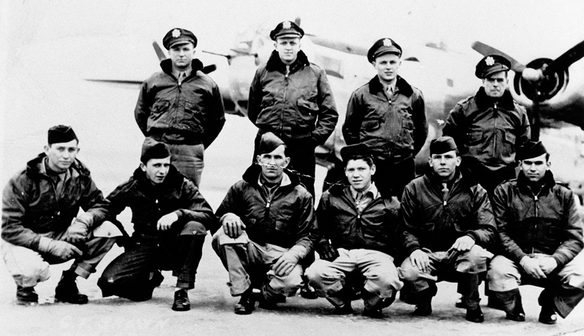 item 4 of Gallery image - a group of ten soldiers stands in front of a plane at a military base during world war two
