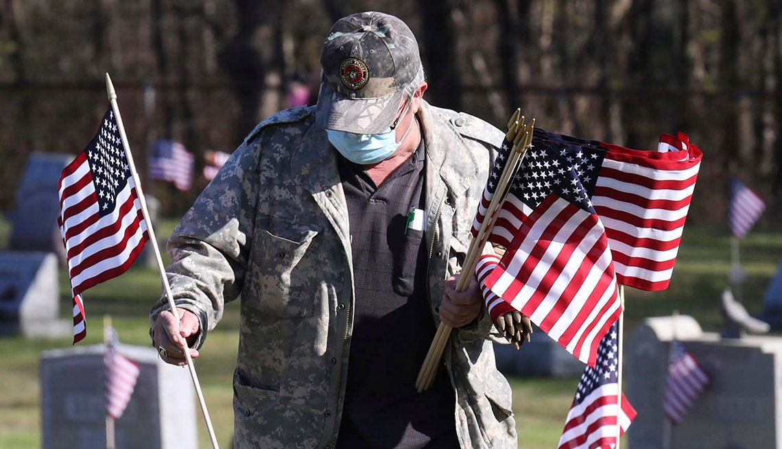 A man wearing a mask places flags on graves