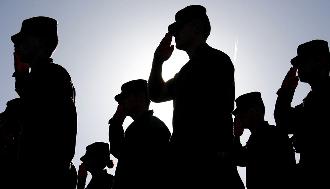 Several soldiers salute the flag