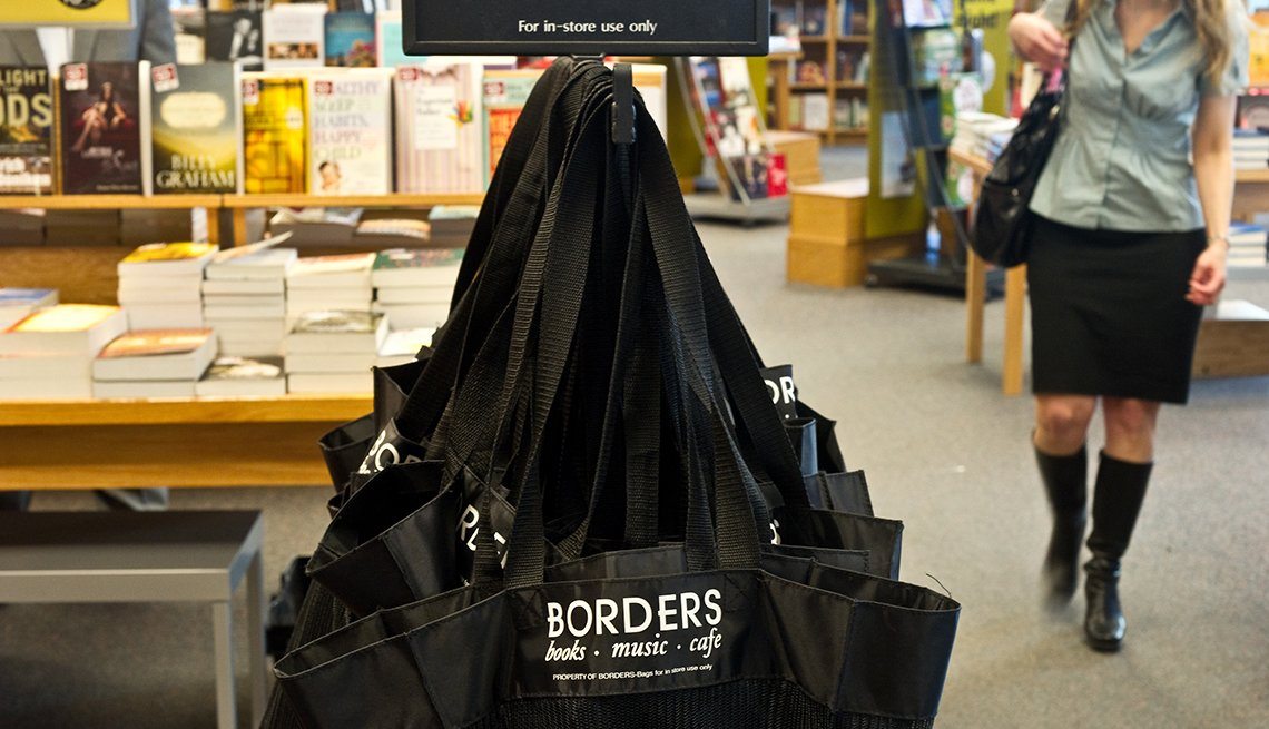 item 9 of Gallery image - scene of a shopper walking in a bookstore with a rack of shopping bags in the foreground