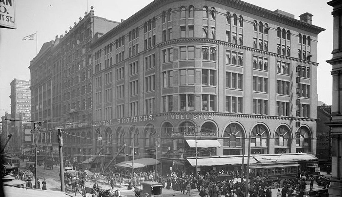 item 14 of Gallery image - old black and white photo taken from across an intersection on a roof or through a high level window of a gimbels department store building on a city street showing people and horse drawn carriages in the street