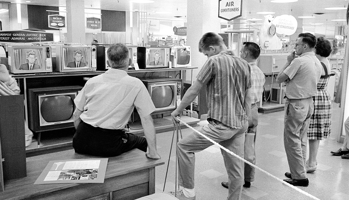 group of customers in a hechts store gather around a television to watch president john f kennedy in this nineteen sixty two photo