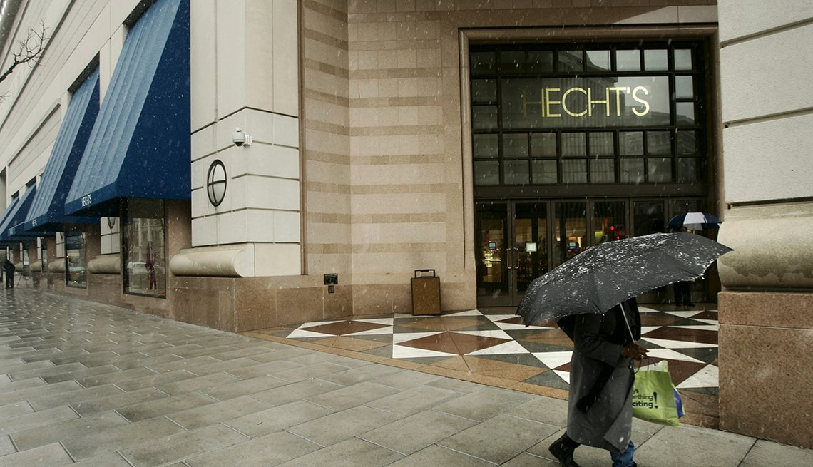 item 10 of Gallery image - a rainy day street scene of a shopper hidden under an umbrella rushing past a hechts department store