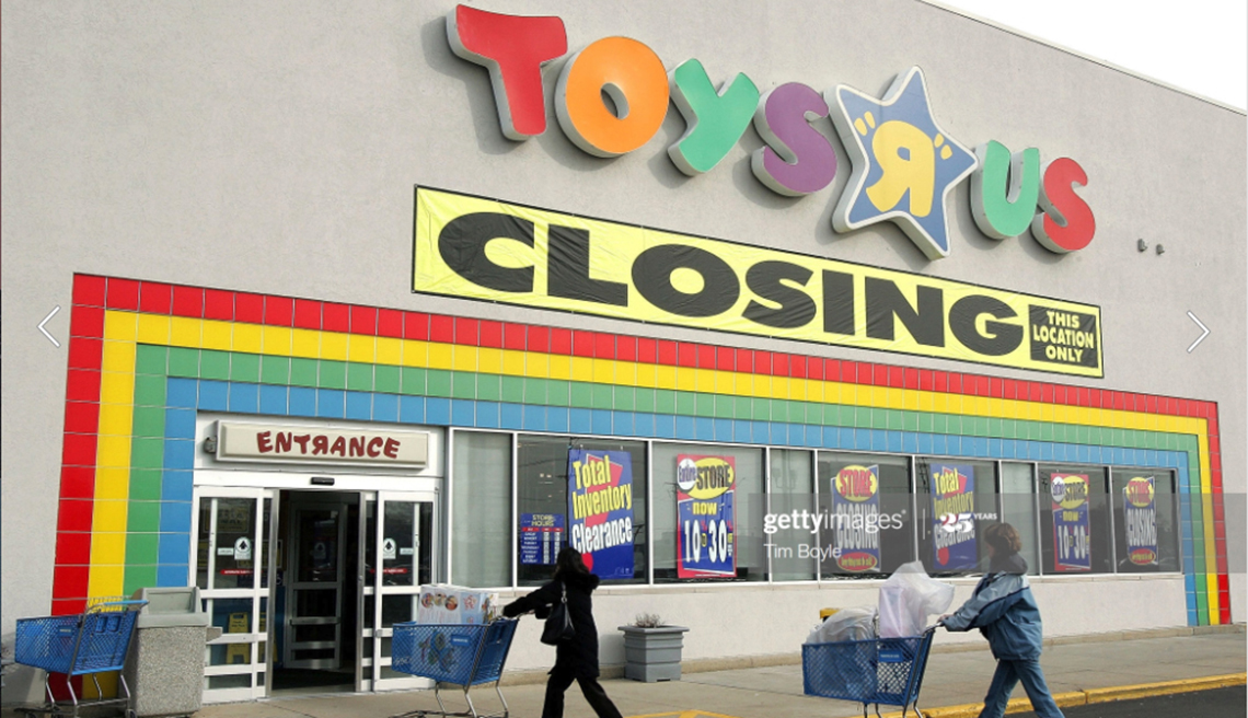 item 3 of Gallery image - the front of a toys r us store showing its sign with a large closing sign under it and two shoppers walking in with carts