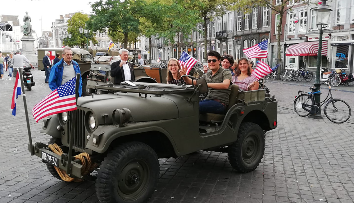 item 9 of Gallery image - a group of young adults in an old military jeep waving american flags in a downtown area with a cobbled street