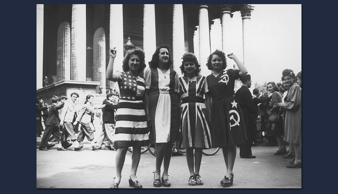 item 7 of Gallery image - four women pose in dresses made to look like the flags of four allied countries at the end of world war two