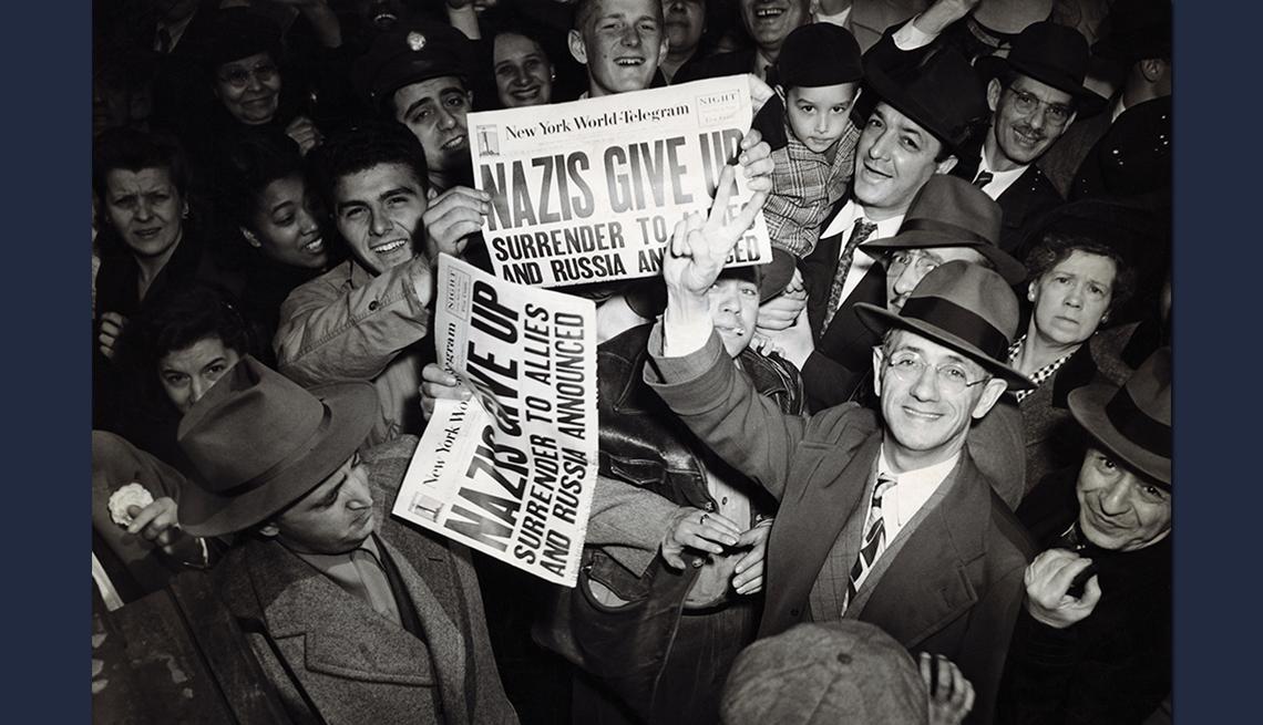 item 4 of Gallery image - Multitud de personas sostienen periódicos proclamando la rendición alemana