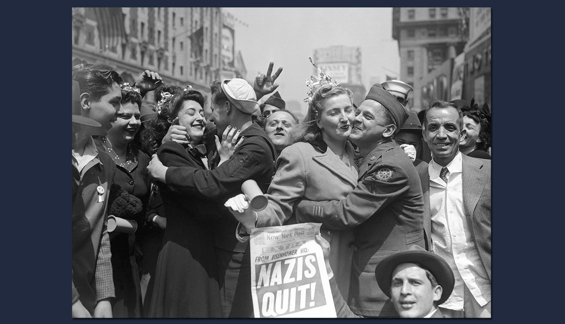crowded street of returning soldiers and others embracing at the announcement of nazi defeat