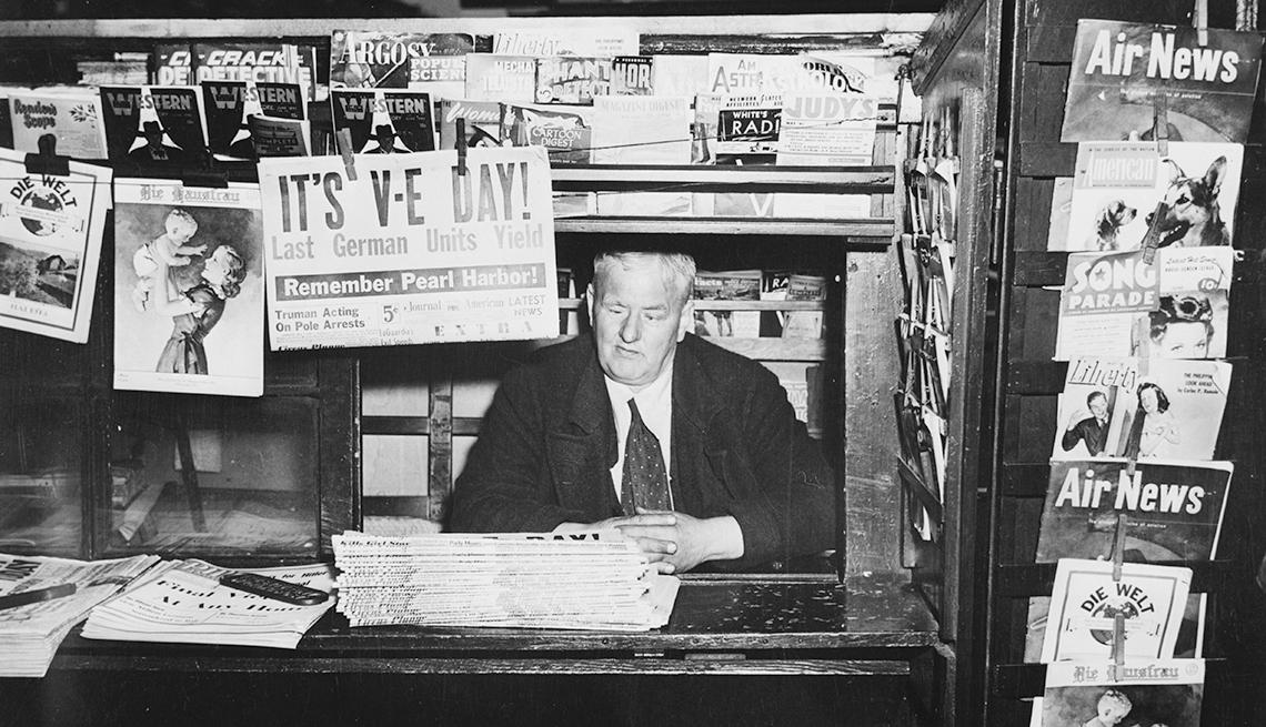 item 1 of Gallery image - Hombre dentro de un quiosco vendiendo periódicos anunciando el V-E Day