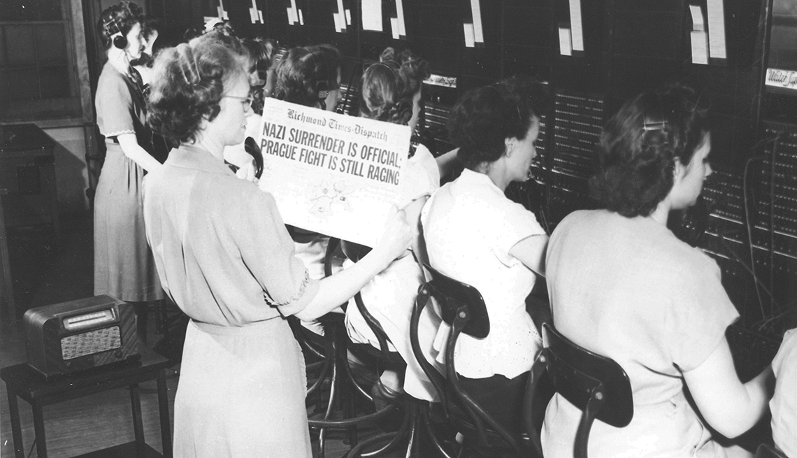 item 3 of Gallery image - telephone operators working during v e day as their supervisor holds up a newspaper showing headline saying nazi surrender
