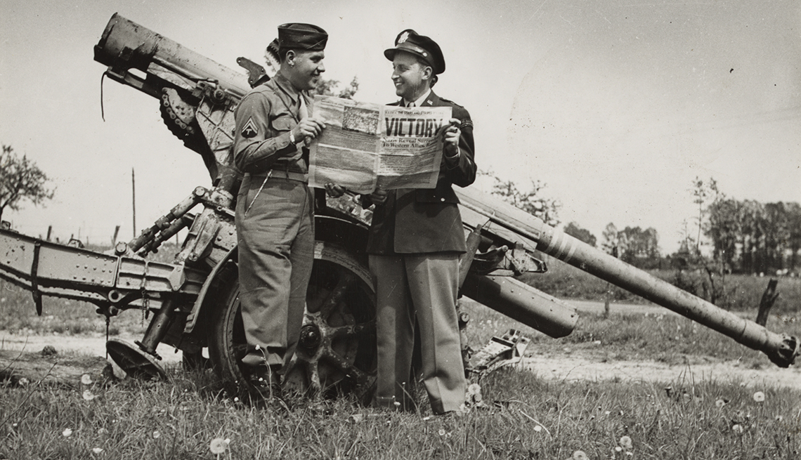 item 2 of Gallery image - two united states soldiers reading a newspaper that has the headline victory in front of a large german gun at the end of world war two