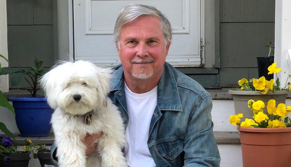Crocker Stephenson sostiene a su perro mientras está sentado en el porche de su casa