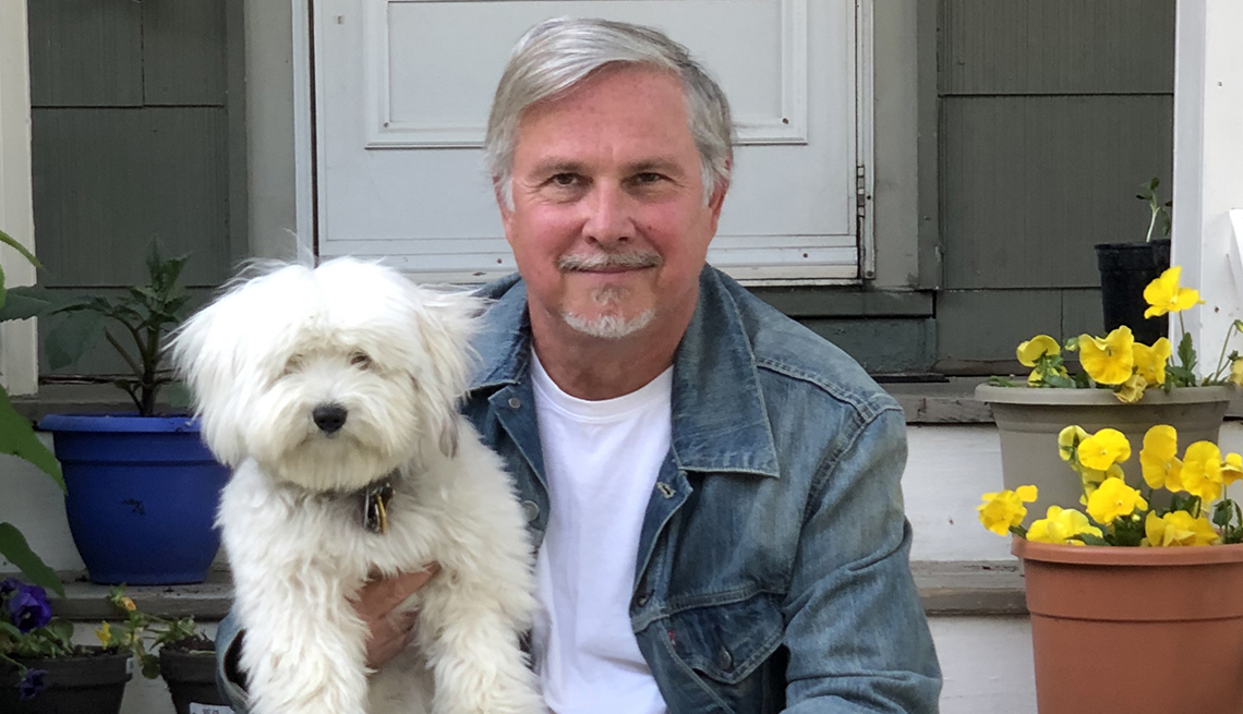 crocker stephenson holding his fluffy dog while sitting on the porch of his home