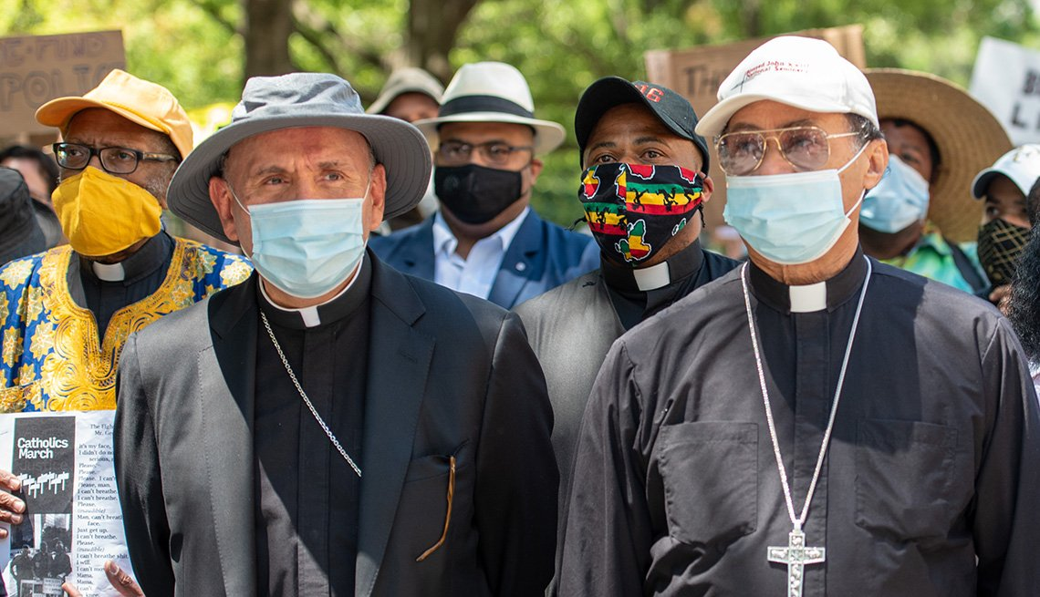 a group of catholic priests wearing face masks are participating in a march for racial justice