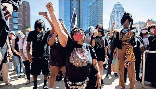 Foto de un grupo de manifestantes con Rhonda Mathies a la cabeza con el puño levantado como un gesto por la justicia racial