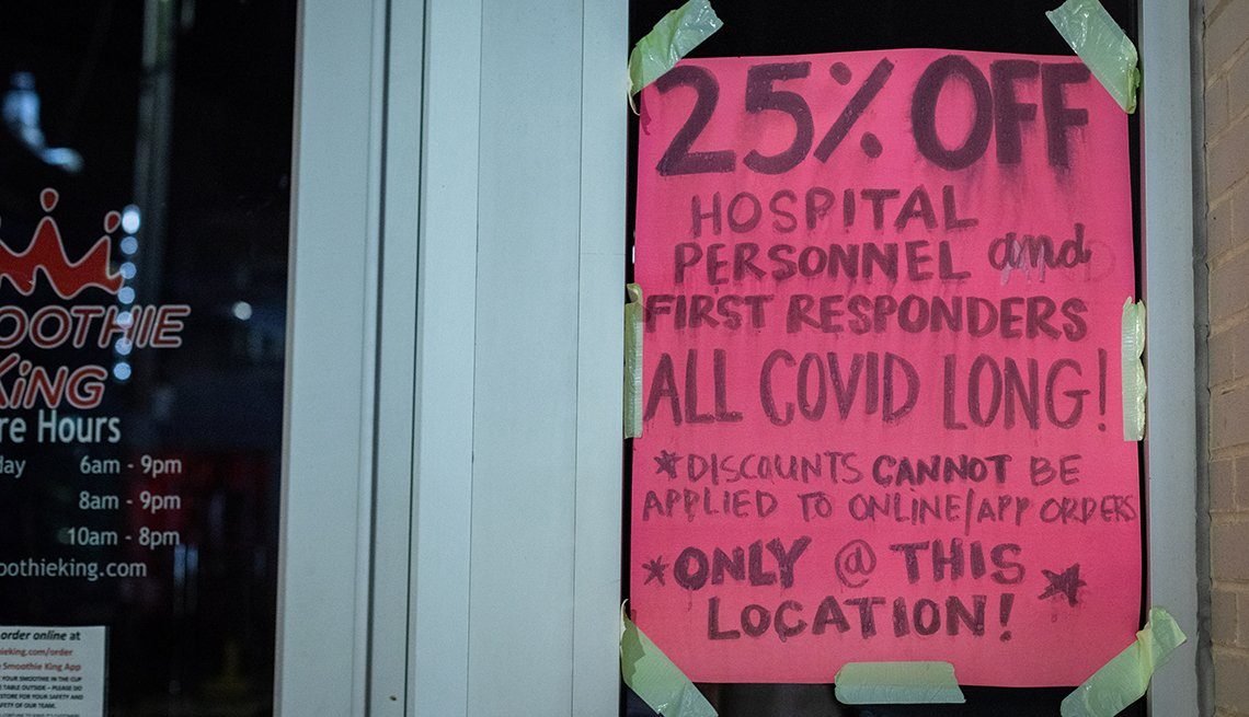 item 8 of Gallery image - sign taped to a storefront communicating a policy of granting a twenty five percent discount for health care workers and first responders