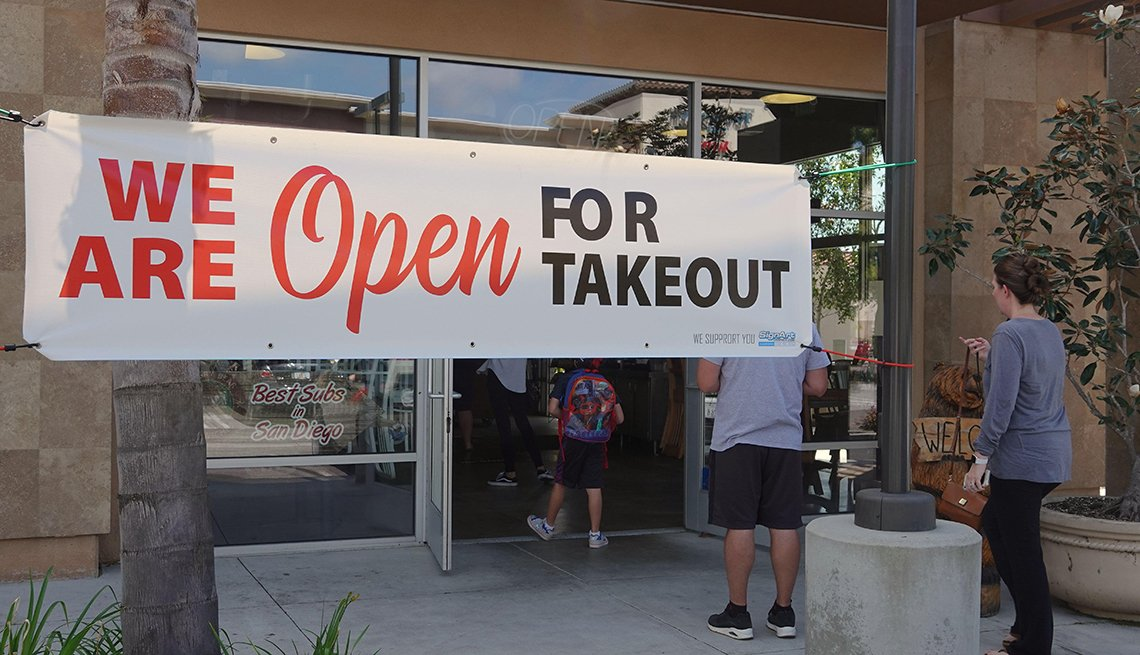 item 3 of Gallery image - sign in front of a store saying they are open for takeout
