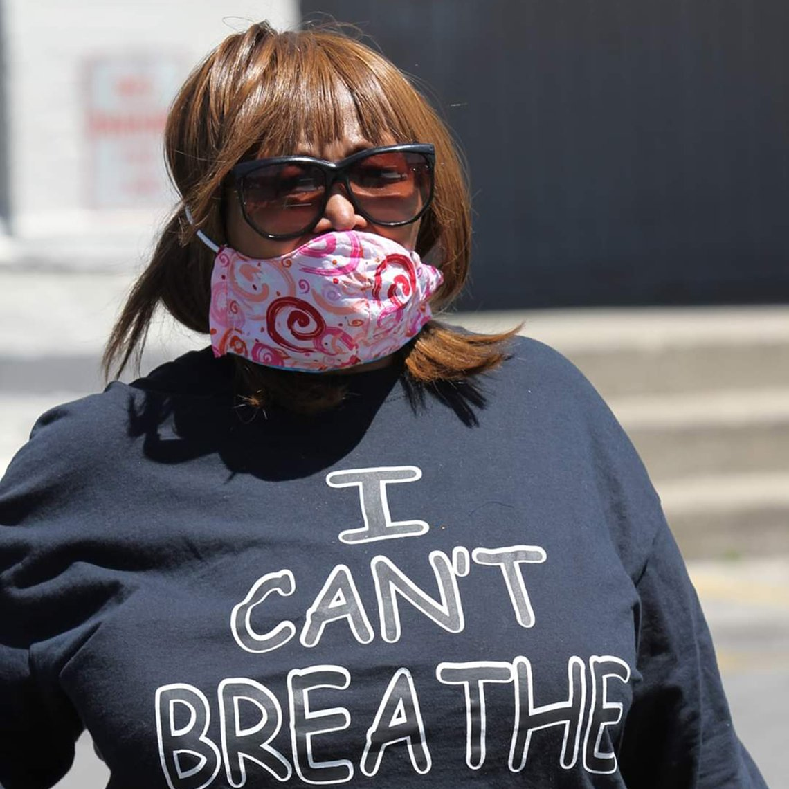 rhonda mathies wearing a face mask and shirt that says i cant breathe at a protest
