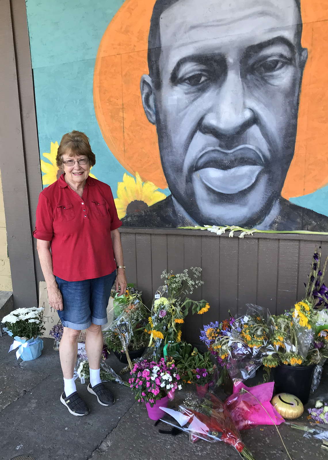 lois knowlton stands next to a memorial mural painted of george floyd that has piles of flowers laid underneath it