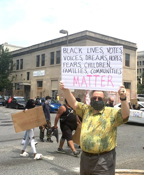 photo of man at protest wearing covid face mask and holding up a sign that reads black lives votes voices dreams hopes fears children families communities matter
