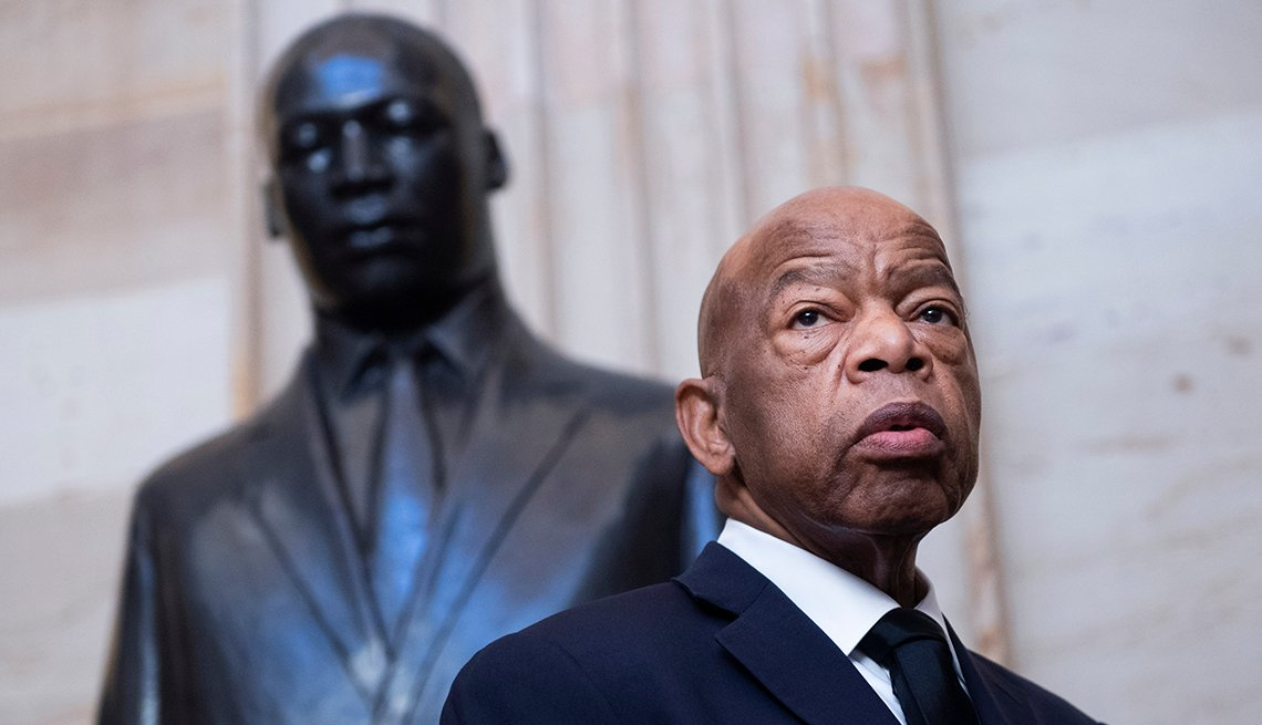 John Lewis stands in front of a statue of Martin Luther King Junior